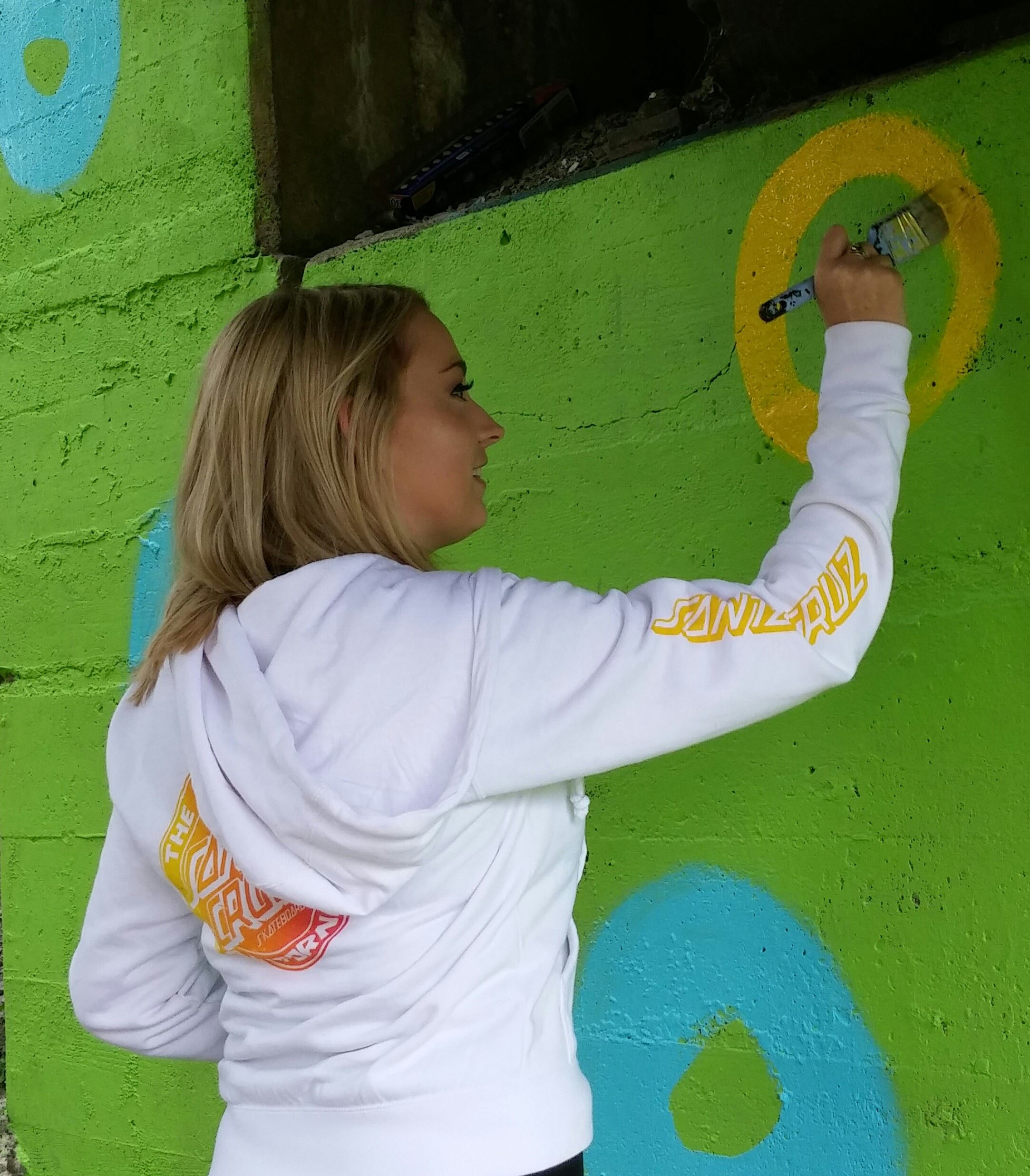 Teenager in white sweatshirt painting a yellow circle on a neon green painted wall