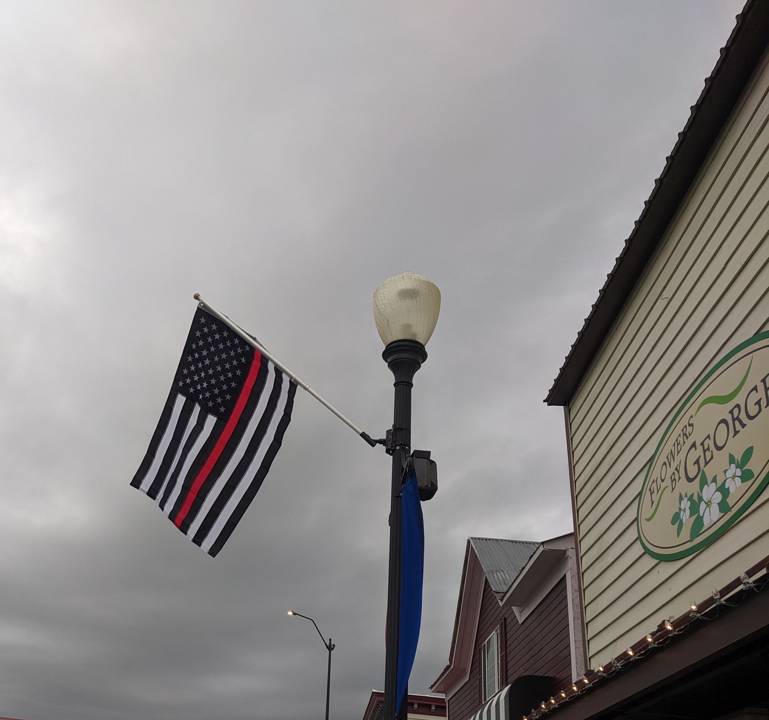 Flag hanging on Olympic Avenue. Flag is 13 black and white alternating horizontal stripes, one red s